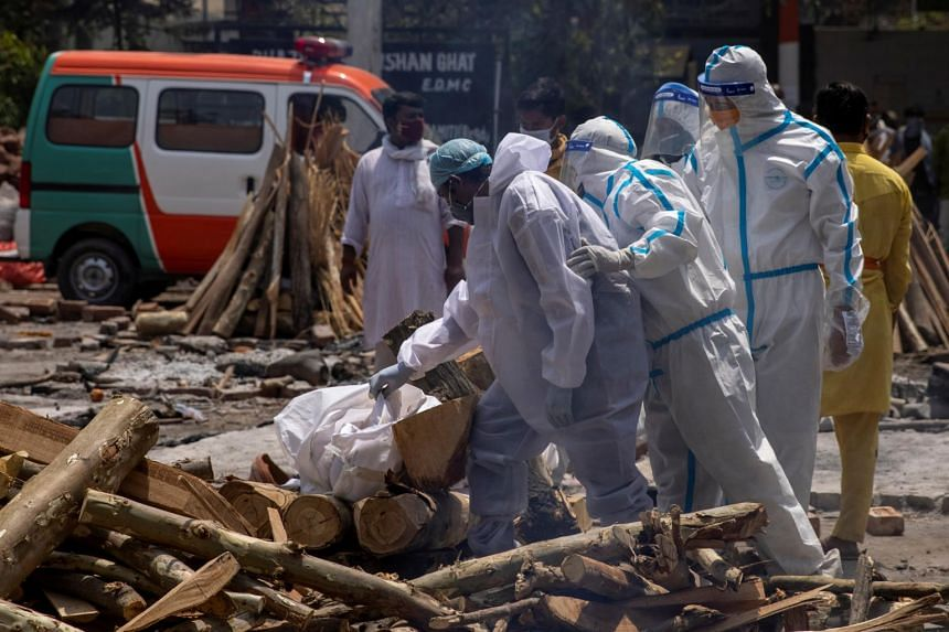 Relatives prepare to cremate the body of a person at a crematorium ground in New Delhi on April 28, 2021.