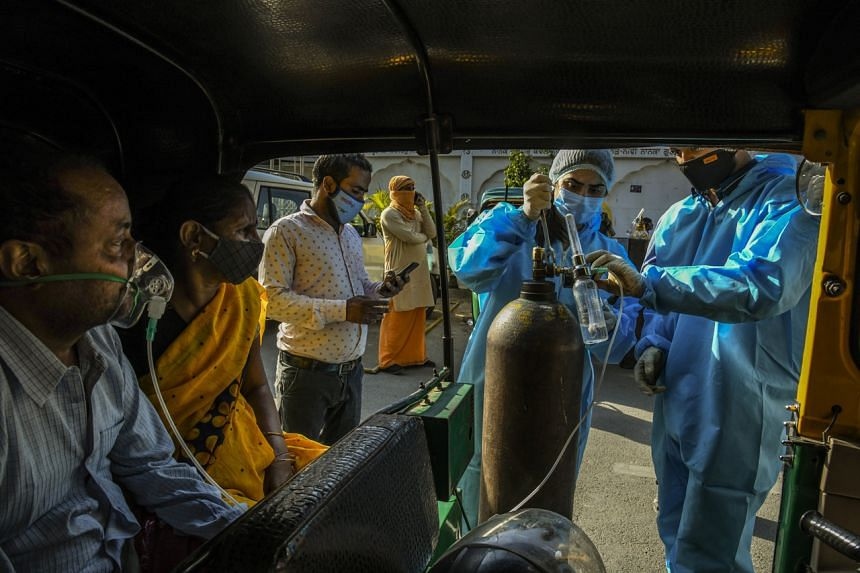 Covid-19 patients sitting in a rickshaw receive oxygen outside a Sikh house of worship in New Delhi on April 25, 2021.