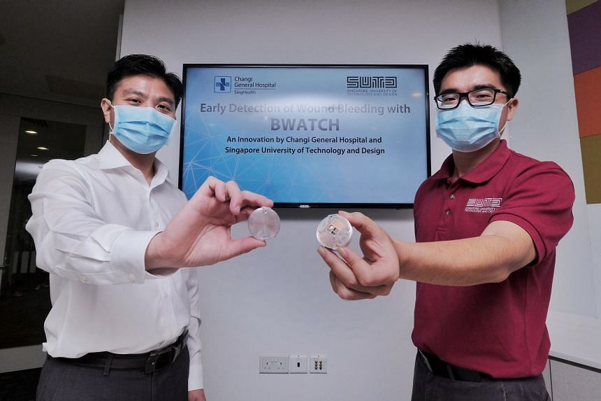 Changi General Hospital's Dr Chionh Chang Yin (left) and SUTD Associate Professor Foong Shaohui showing the monitoring device that is placed over a patient's bandage.