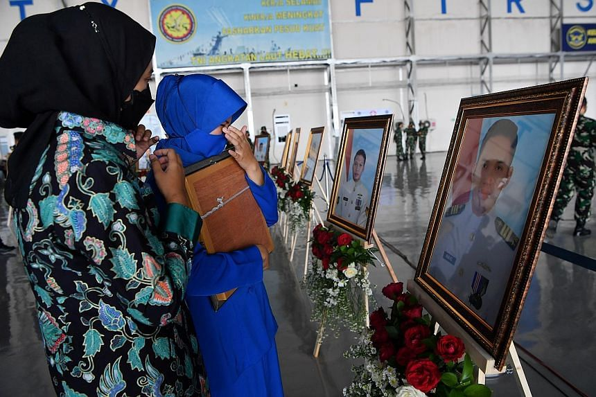 Relatives of a crew member of the sunken Indonesian submarine in front of his portrait during a posthumous promotion ceremony yesterday for all the 53 who perished last week. President Joko Widodo, who officiated at the ceremony in Sidoarjo, East Jav