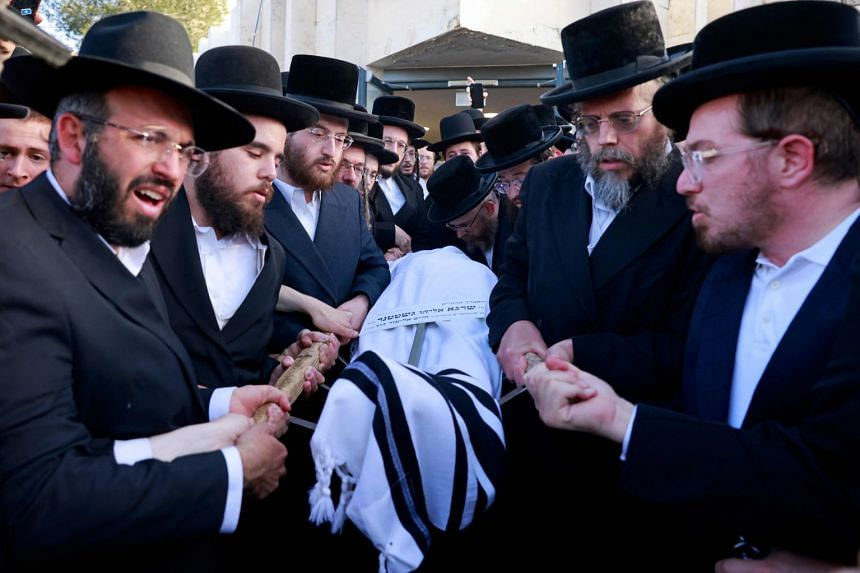 Ultra-Orthodox Jewish mourners carry the body of a victim of the stampede during a funeral ceremony in Jerusalem.