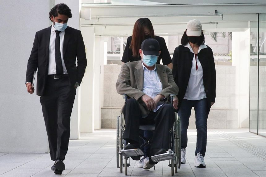 O.K. Lim (in wheelchair) arriving in court on Friday morning with his lawyer, Mr Navin Thevar (left).