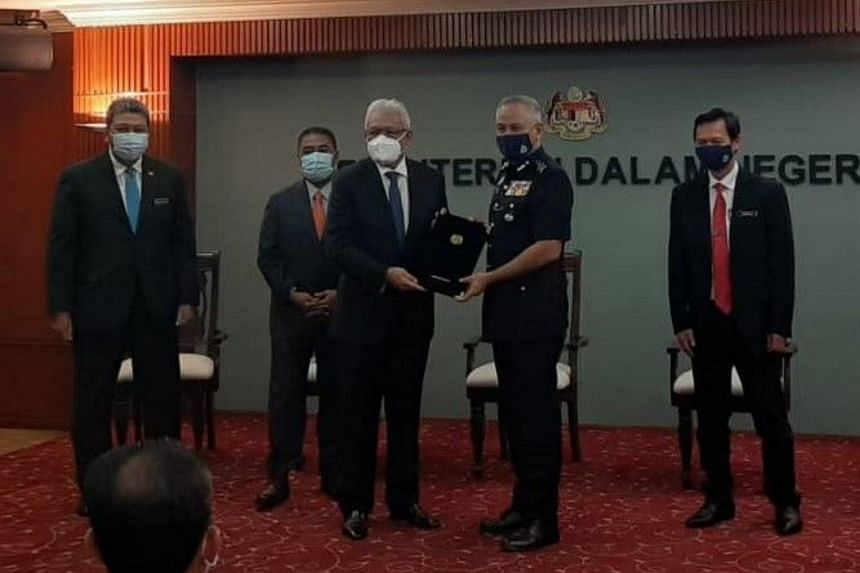 Datuk Seri Acryl Sani Abdullah Sani receiving his letter of appointment from Home Minister Hamzah Zainudin (left).