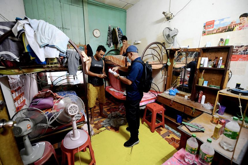An official checking on migrant workers at the Bukit Tengah industrial zone in Penang in January, in a bid to enforce compliance with legislation on the minimum standards for worker accommodation.
