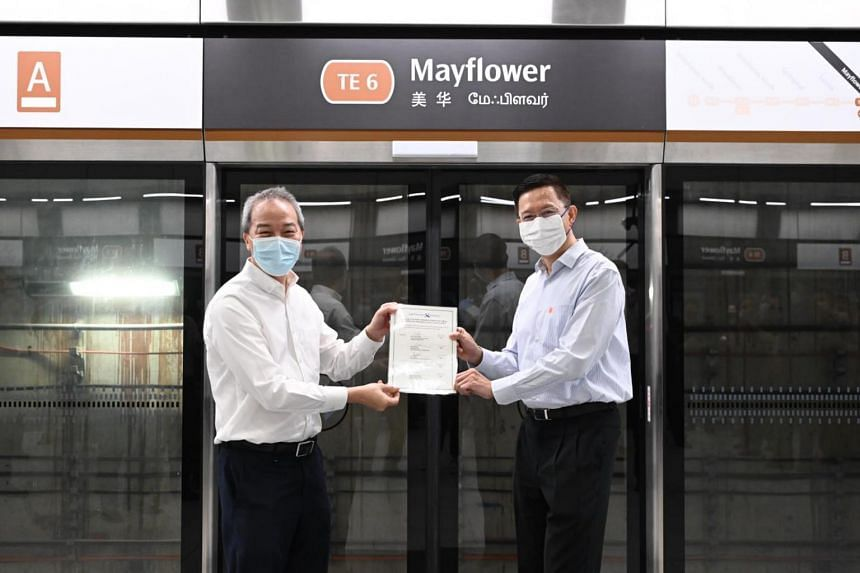 LTA CEO Ng Lang (left) presenting the handover certificate to SMRT Group CEO Neo Kian Hong at Mayflower station on April 30, 2021.