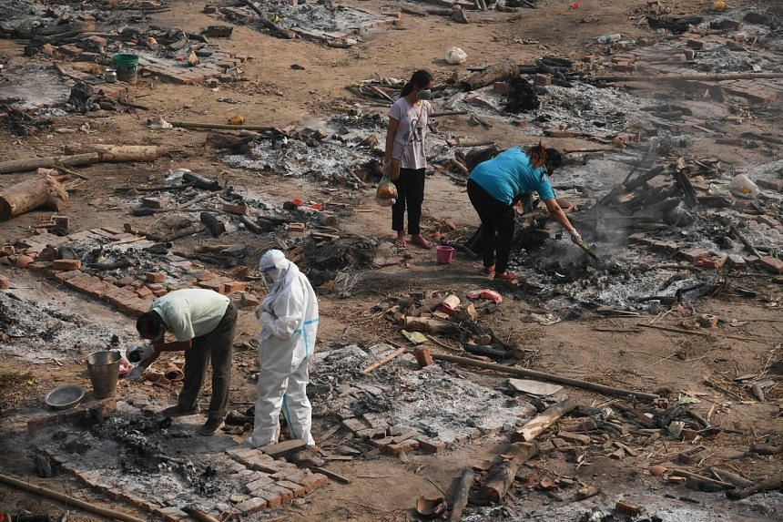 Relatives collect the remains of Covid-19 victim after a mass cremation at a cremation ground in New Delhi on April 30, 2021.