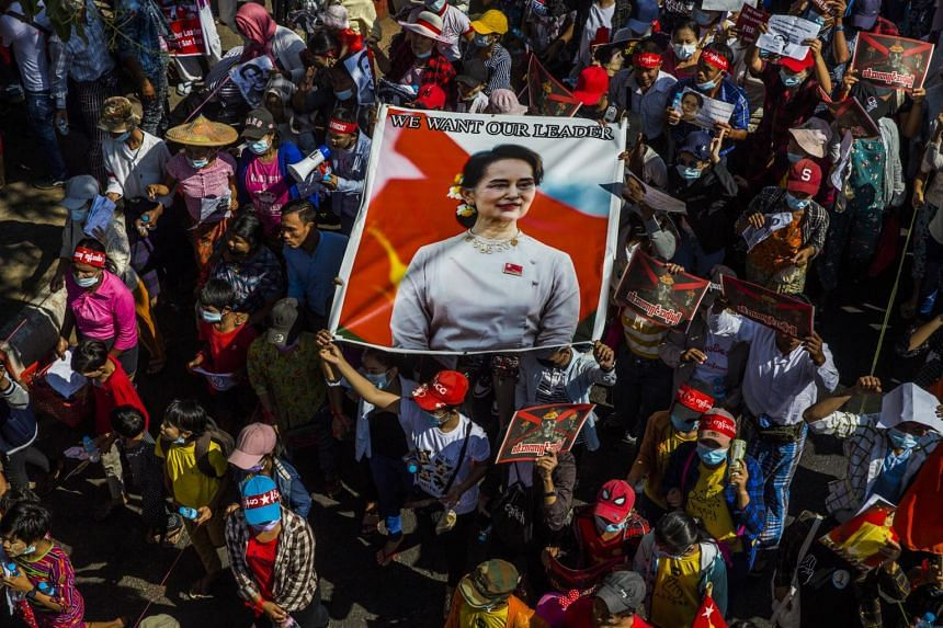 Demonstrators carry a banner of Aung San Suu Kyi during protests against the military coup in Yangon on Feb 13, 2021.