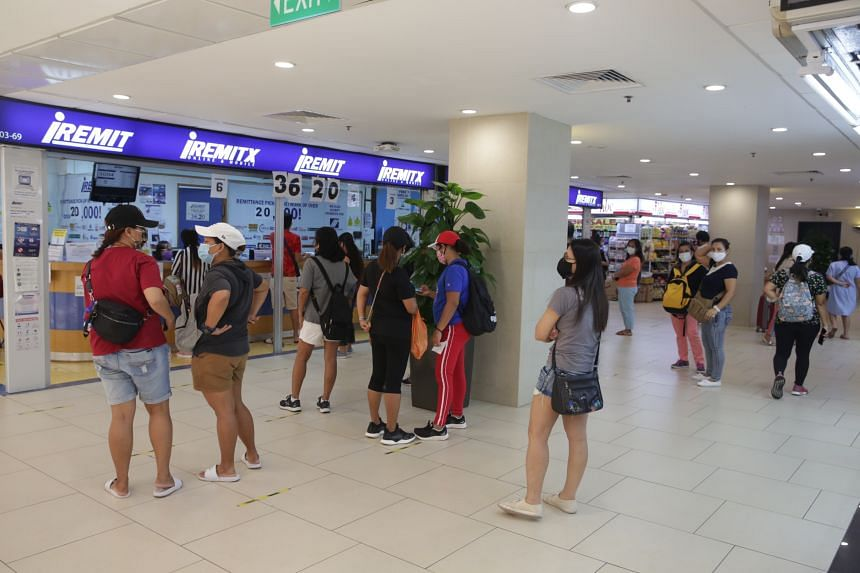 Migrant and domestic workers queueing for remittance and courier services at Lucky Plaza on May 1, 2021.