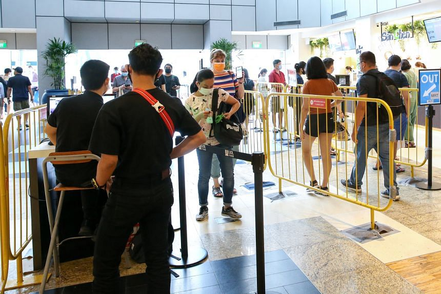 Shoppers scanning their TraceTogether token and SafeEntry QR codes to enter Velocity @ Novena Square on May 1, 2021.