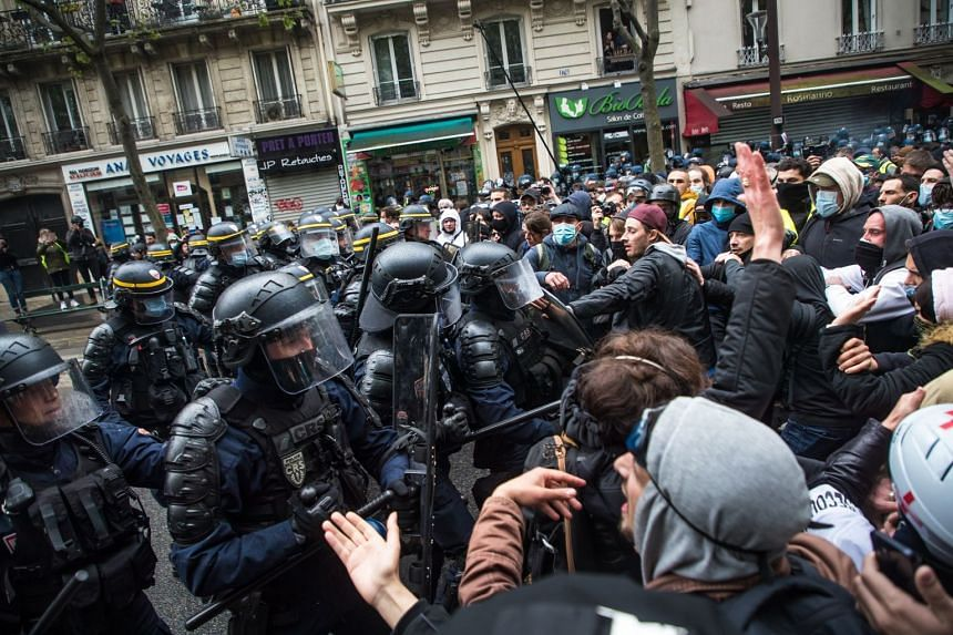French anti-riot police face protesters as clashes erupt during a May Day march in Paris.