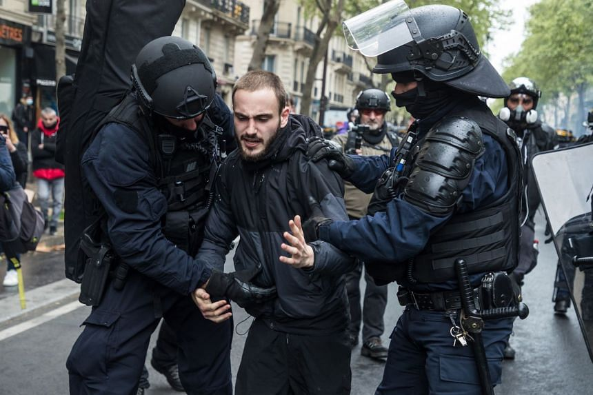 A protester is detained by riot police as clashes erupt during the annual May Day march in Paris.