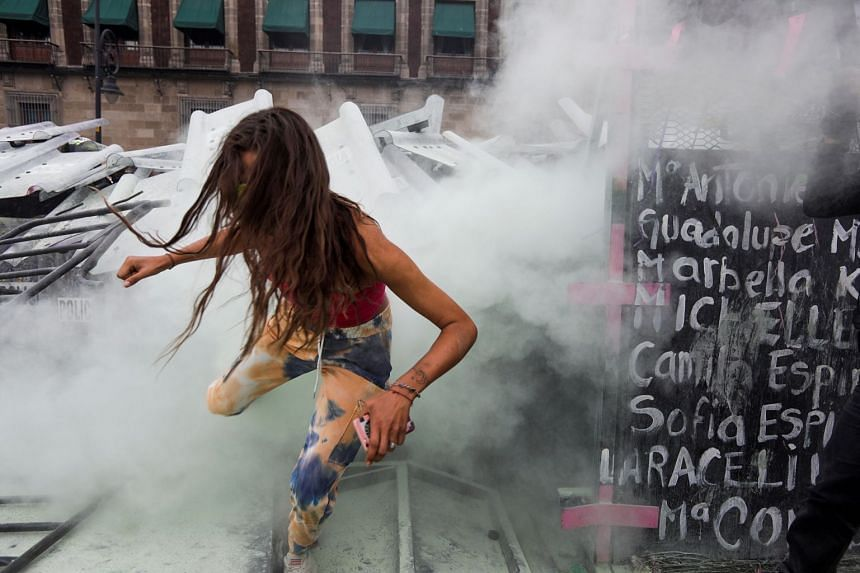 A woman runs from tear gas during a protest on International Women's Day in Mexico City, on March 8, 2021.