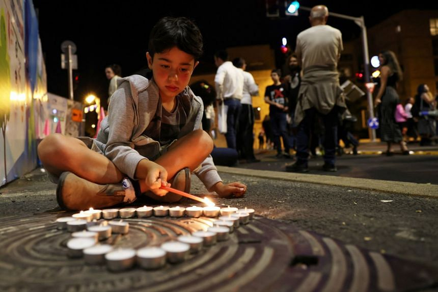 A boy lights candles during a vigil for the people killed and injured in the stampede, in Jerusalem, on May 1, 2021.