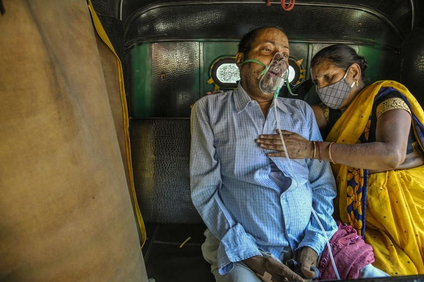 A relative helps a man sitting in the back of a motorised rickshaw receive oxygen for his Covid-19 symptoms, in Delhi, India, on April 25, 2021.