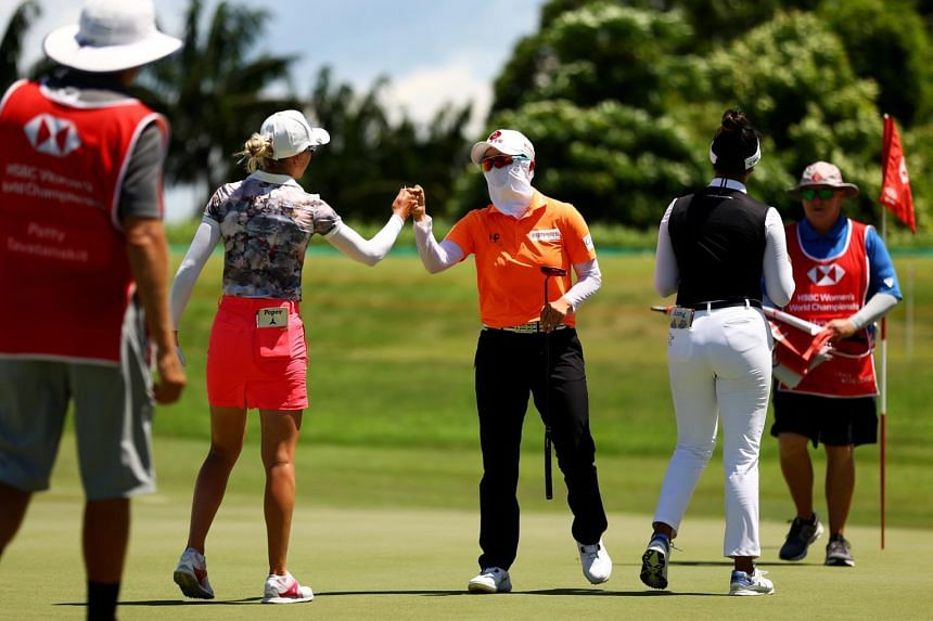 South Korea's Hyo-joo Kim bumps fists with Germany's Sophia Popov after completing the final round of the HSBC Women's World Championship at Sentosa Golf Club on May 2, 2021.