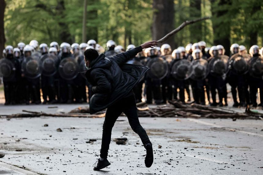 A protester throws a projectile at riot police during the protest party in Bois de La Cambre park in Brussels.