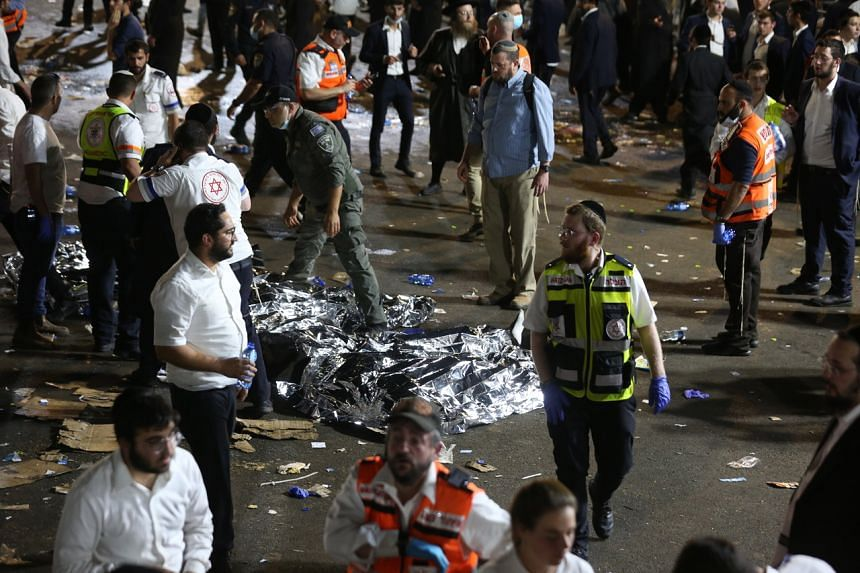 Security officials and rescuers inspect the bodies of Ultra-Orthodox Jews who died during an event at a revelry complex during Lag BaOmer, in Mount Meron, Israel, on April 29, 2021.