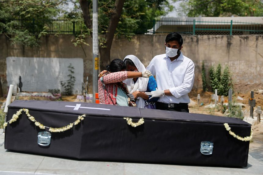 From left: Relatives collecting the remains of Covid-19 victims after a mass cremation in New Delhi on Friday; Ms Shruti Saha, who had been waiting since Tuesday night for her turn to refill an oxygen cylinder for her mother, breaking down after hear
