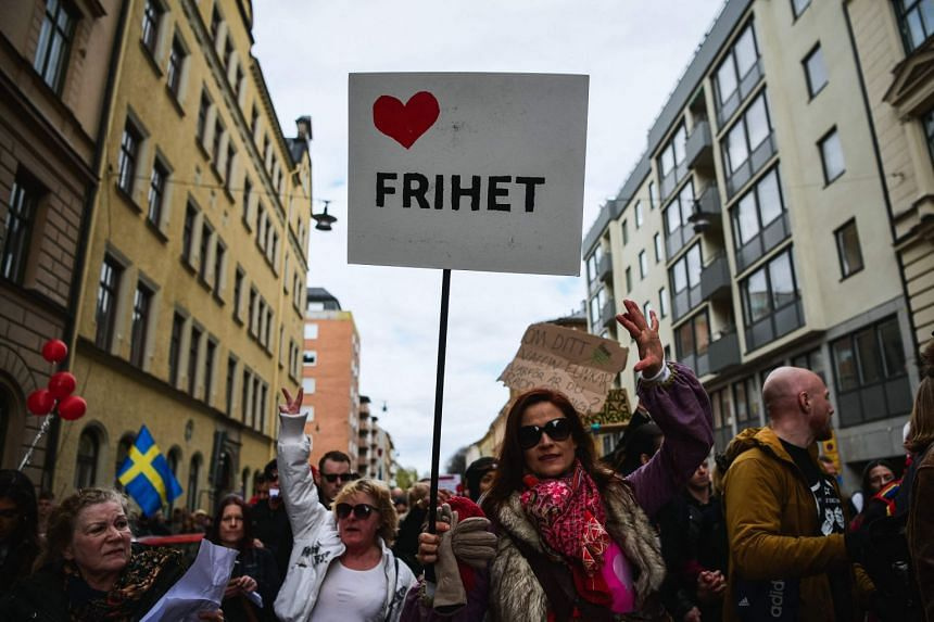 """A woman holds a sign reading """"freedom"""" as she attends a march through the streets of Stockholm."""
