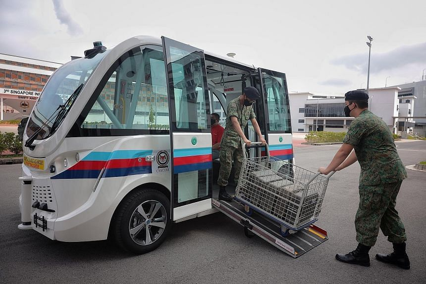 Servicemen loading jerry cans onto an autonomous vehicle in Kranji Camp III. A safety operator will be on board the vehicle - which has a maximum operating speed of 18kmh - at all times during the trial period. ST PHOTO: JASON QUAH