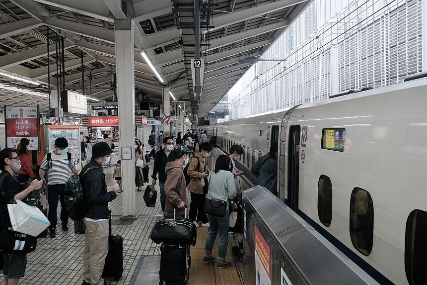 Passengers boarding a bullet train in Tokyo at the start of the Golden Week holidays last Thursday, amid a state of emergency. Japan logged 5,879 new Covid-19 cases yesterday as its overall tally crossed 600,000.