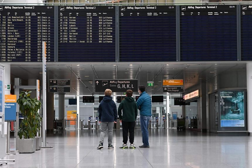 Passengers stand in front of a display board in a terminal of the Franz-Josef-Strauss airport in Munich, on April 8, 2021.