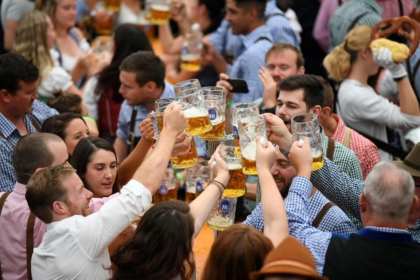 In a file photo from Sept 22, 2019, visitors cheer with beers in a tent during Oktoberfest in Munich.