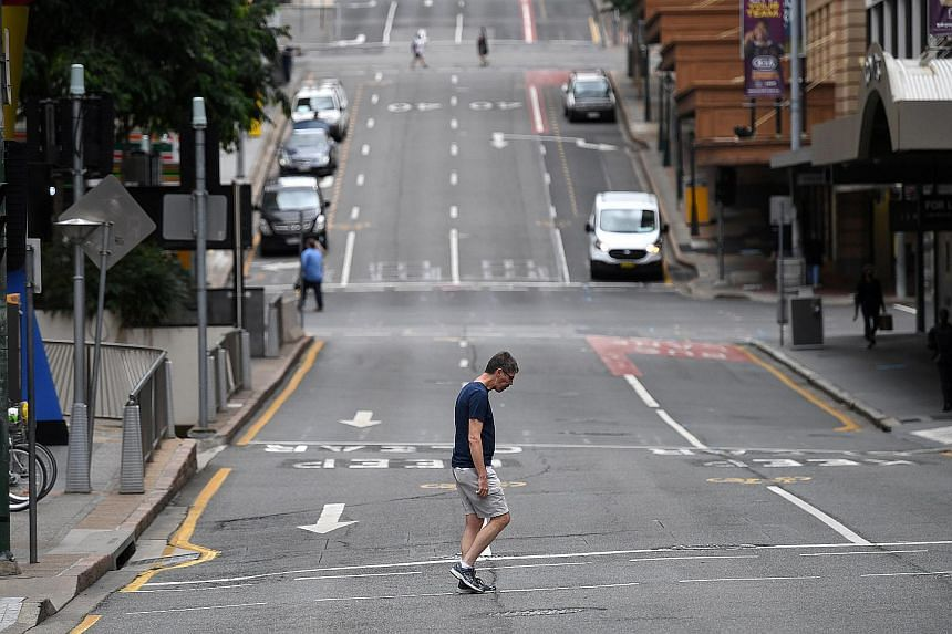 A man crosses a mostly empty city centre street as people in Greater Brisbane have been ordered into lockdown, on March 30, 2021.