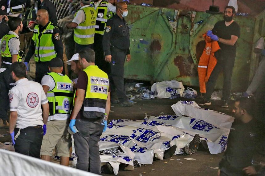 Paramedics and ultra-Orthodox Jewish men stand next to covered bodies after dozens of people were killed in Meron, Israel, early on April 30, 2021.