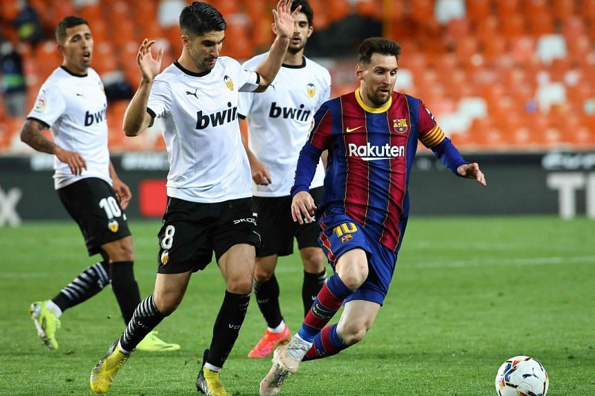 Valencia's Carlos Soler (second left) challenges Barcelona's Lionel Messi on May 2, 2021.