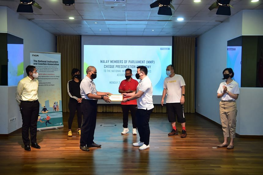 Mr Masagos presenting the cheque to Mr Adrian Chiang.