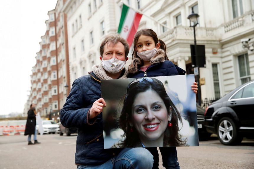 Richard Ratcliffe, husband of British-Iranian aid worker Nazanin Zaghari-Ratcliffe, and their daughter Gabriella protest outside the Iranian Embassy in London, on March 8, 2021.