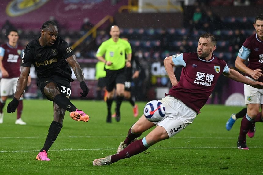 West Ham's Michail Antonio (left) in action against Burnley's Charlie Taylor (right) on May 3, 2021.