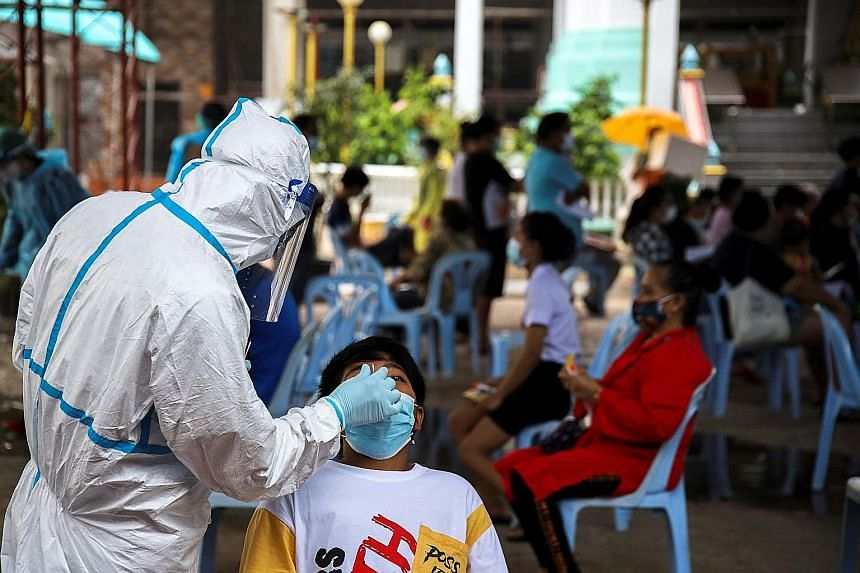 A swab test being administered in Bangkok yesterday. The new outbreak has accounted for more than half of total cases and deaths in Thailand since the start of the pandemic.