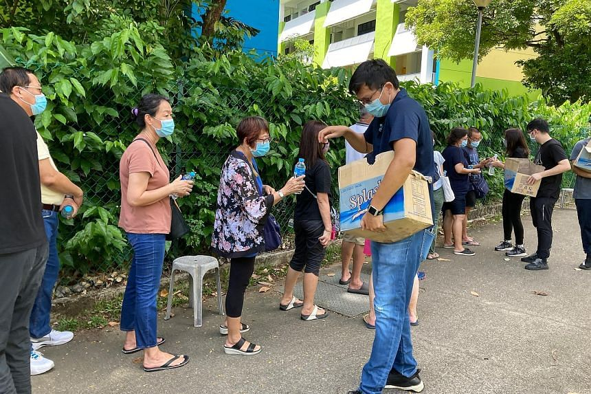 Bottled water being given to those queueing for Covid-19 tests at the former Da Qiao Primary School in Ang Mo Kio yesterday. By 11am, there were over 300 people in a line stretching 300m away from the facility.