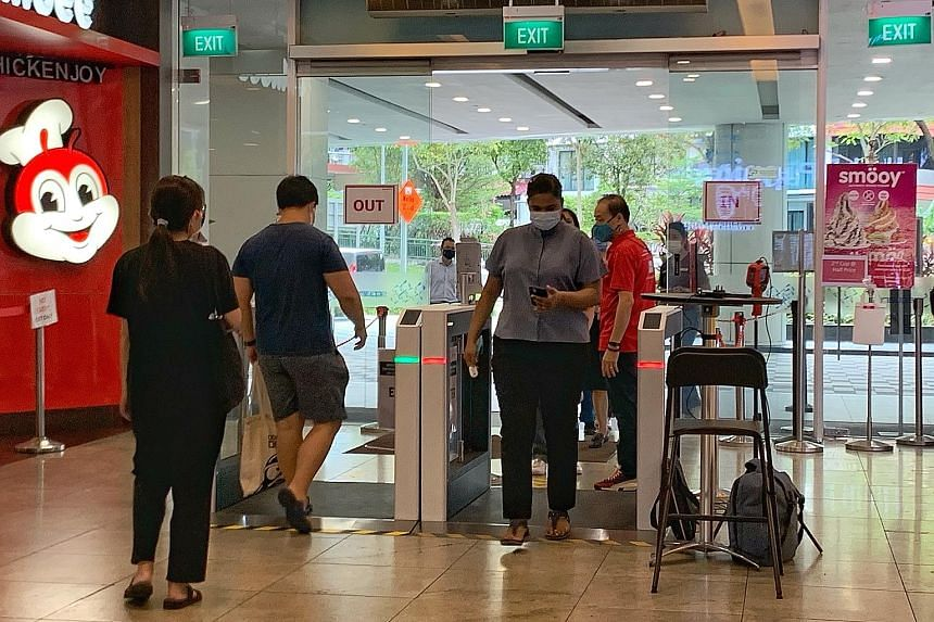 Visitors using the automated self-check-in gantry system at Square 2 shopping mall in Novena yesterday. The system ensures they check in with SafeEntry, and the gantry has cameras that measure body temperature.