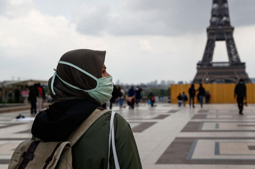 A woman wearing a hijab walks at Trocadero square near the Eiffel Tower in Paris, on May 2, 2021.