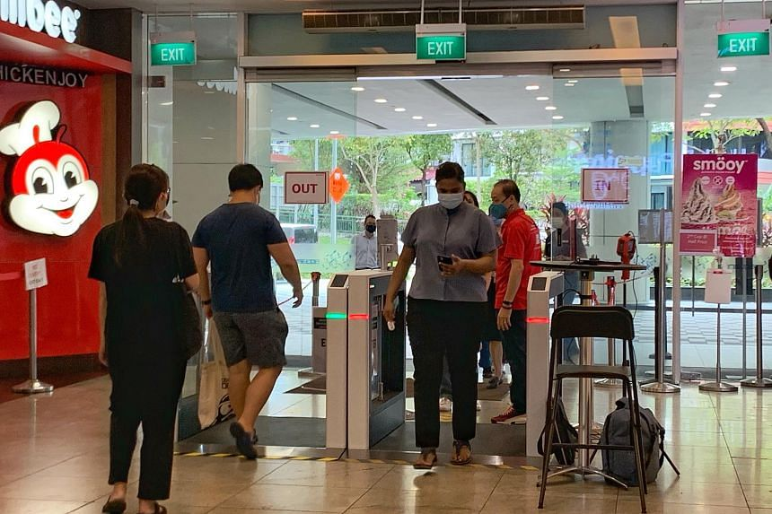 People using the self check-in automated SafeEntry station at Square 2 shopping mall, on May 3, 2021.