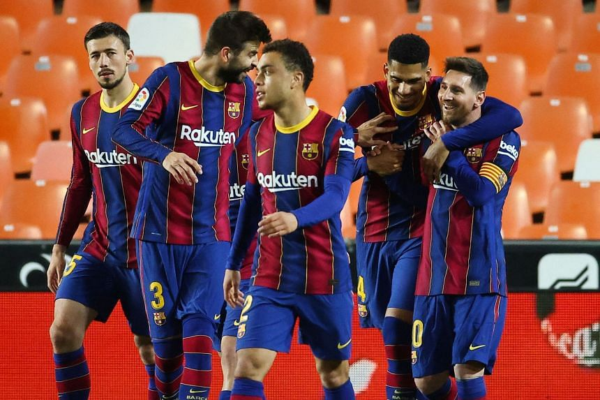Messi (right) celebrates with teammates after scoring his second goal during Barcelona's La Liga match against Valencia on May 2, 2021.