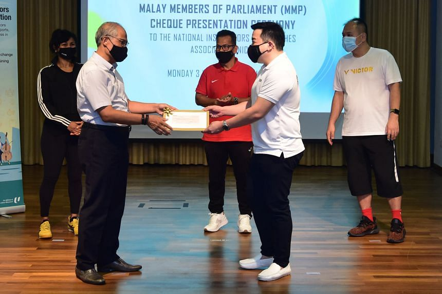 Minister for Social and Family Development Masagos Zulkifli presenting the cheque on behalf of 12 Malay PAP MPs yesterday to Mr Adrian Chiang, president of the National Instructors and Coaches Association.