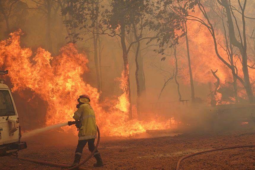 A firefighter fighting a blaze outside Wooroloo, near Perth, on Feb 2, 2021. Australia has had to deal with a spate of natural disasters in recent years.