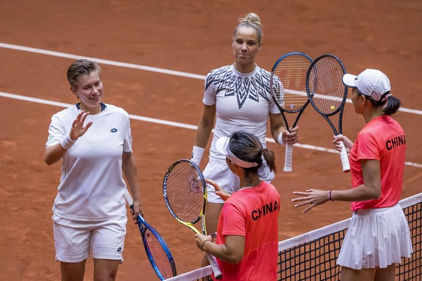 Players from the Netherlands and China greet during the Billie Jean King Cup Play-off in Den Bosch, the Netherlands, on April 17, 2021.