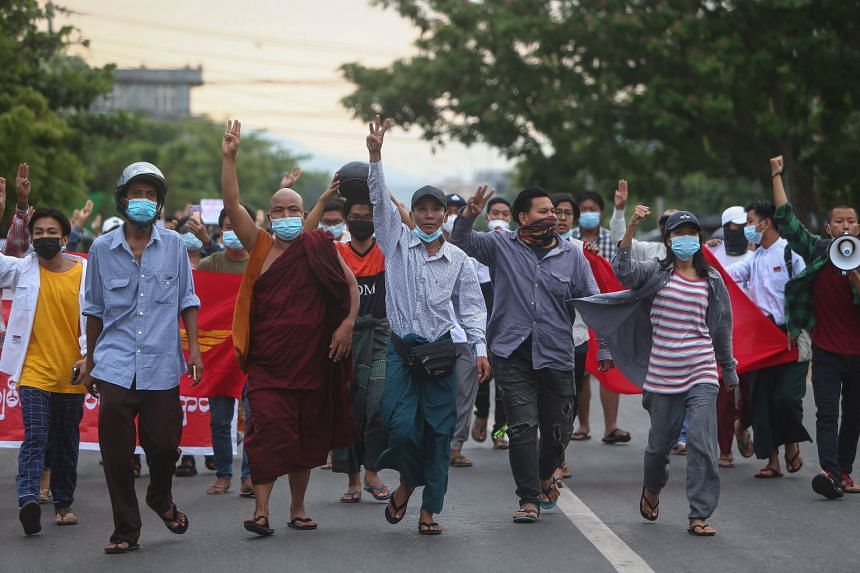 Demonstrators flash the three-finger salute during an anti-military coup protest in Mandalay, on May 3, 2021.