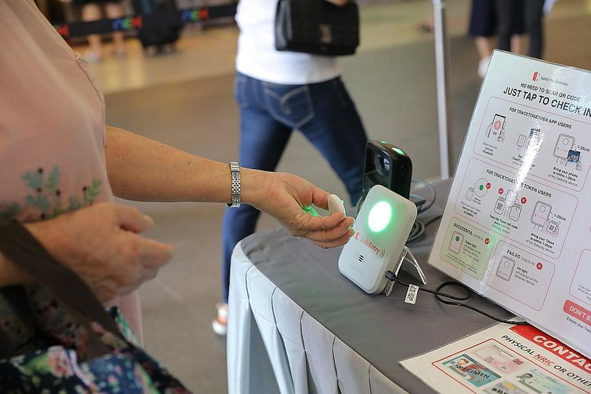 A shopper using the TraceTogether token to check in at a mall. From May 17, people will no longer be able to use other modes of SafeEntry check-in - such as scanning a SafeEntry QR code with a phone camera or the Singpass app - which will be disconti