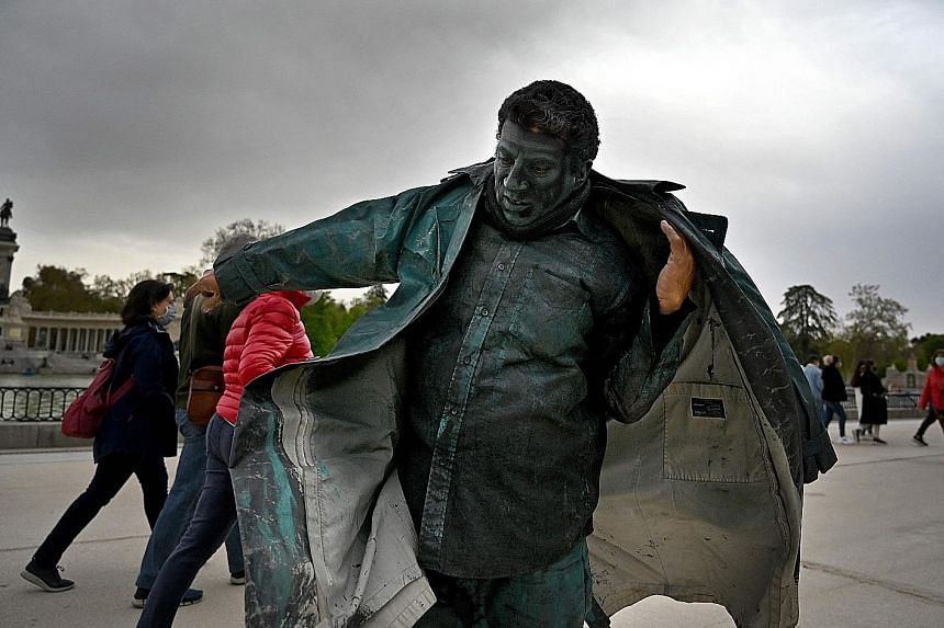 Shoes in matching hues (left) are a must for Cuban street performer Ricardo Elias Hardy (above), who dresses himself up (right) to play a living statue (below) at the Retiro park in Madrid, Spain. His performance requires him to stand motionless and