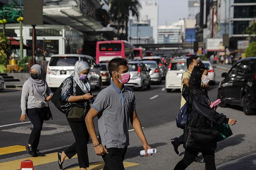 Pedestrians in Kuala Lumpur, Selangor, yesterday. Covid-19 cases in Malaysia have breached the 3,000 mark in five of the last seven days, and the government is placing six districts in the densely populated Selangor state under the first-tier movemen