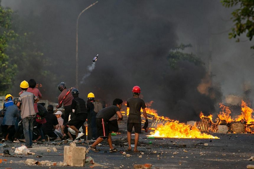 A protester throws a petrol bomb during a crackdown on demonstrations against the military coup in Yangon, on March 16, 2021.