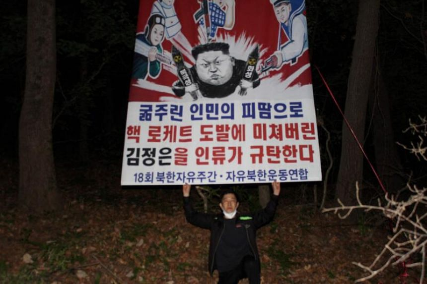 Chairman of Free North Korea, Park Sang-ha, releasing a banner with a cartoon depicting North Korean leader Kim Jong Un attached to a balloon, at an undisclosed location near the Demilitarized Zone (DMZ) dividing the two Koreas.
