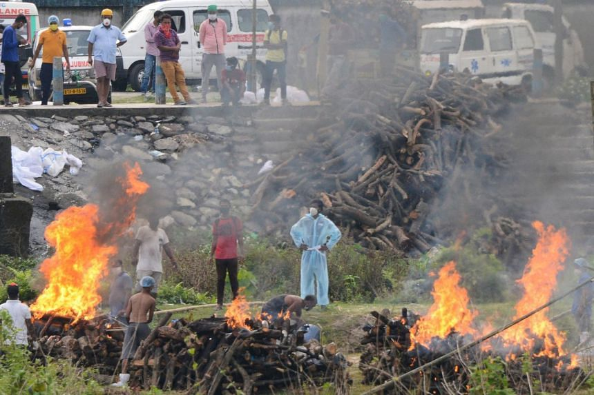 People watching the cremation of people who died due to Covid-19 in West Bengal, India, on May 4, 2021.