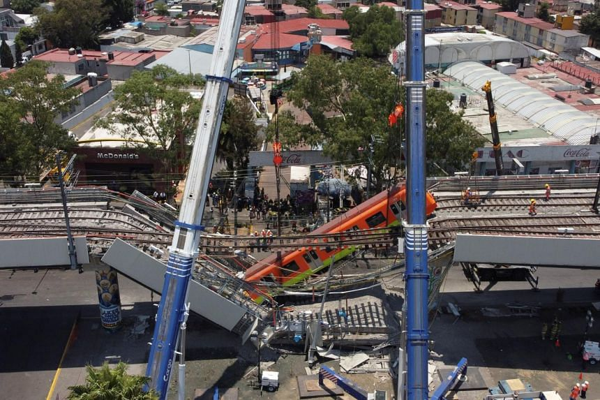 A general view of cranes removing the crashed coach after a railway overpass and train collapsed onto a road in Mexico City, on May 4, 2021.